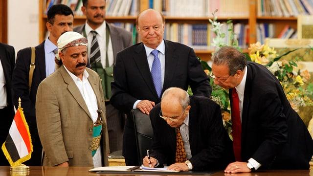Männer an einem Tisch, einer bückt sich um eine Unterschrift zu leisten.