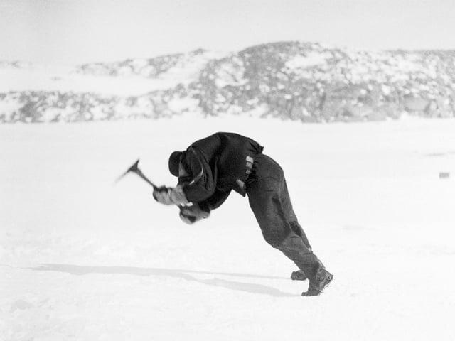 Ein Mann schlägt mit einem Bickel ins Eis.
