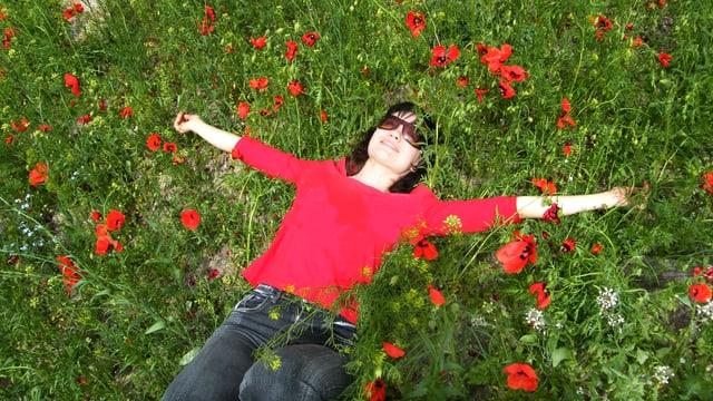 Eine Frau liegt strahlend und glücklich auf einer Wiese, aus der rote Blüten wachsen.