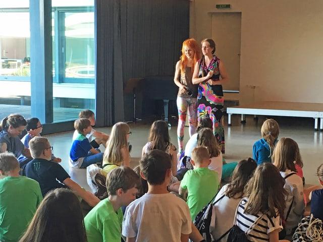 Zwei Frauen stehen vor einer Gruppe sitzender Kinder.