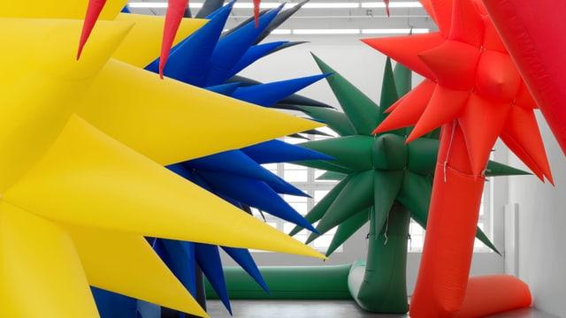 Riesige bunte aufblasbare palmenförmige Skulpturen in einer Ausstellungshalle.