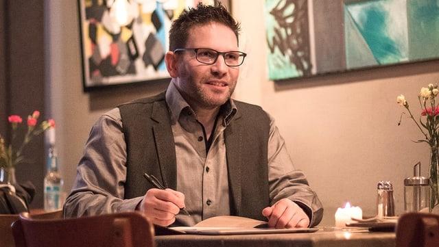 Ein Mann mit Brille und Hemd sitzt an einem Tisch mit einem Kugelschreiber in der Hand.