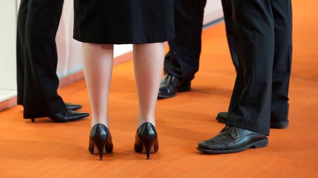Eine Frau und drei Männer stehen im Kreis, man sieht nur die Beine.
