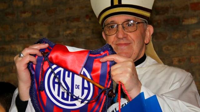 Papst Franziskus mit einem Trikot des argentinischen Fussballclubs Club Atlético San Lorenzo de Almagro in den Händen.