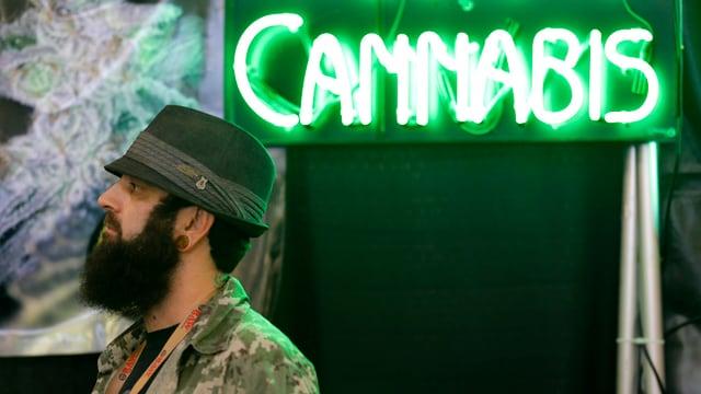 In um cun barba che stat avant in club che ha num Cannabis.