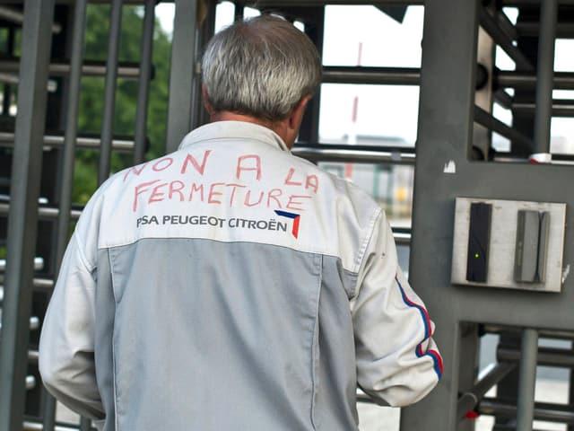 PSA-Arbeiter im Overall, darauf steht: Non a la fermeture