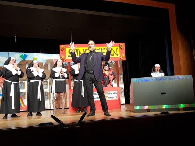 Ein Pfarrer steht vorne und scheint eine flammende Predigt zu halten, im Hintergrund sieht man drei Nonnen, eine in Netzstrümpfen und kurzem Kleid.