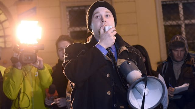 Ein Mann spricht in ein Mikrofon