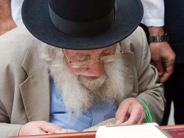 ein alter Mann mit Bart und Schwarzem Hut liesst mit einer goldenen Brille aus einem Judischen Gebetsbuch.