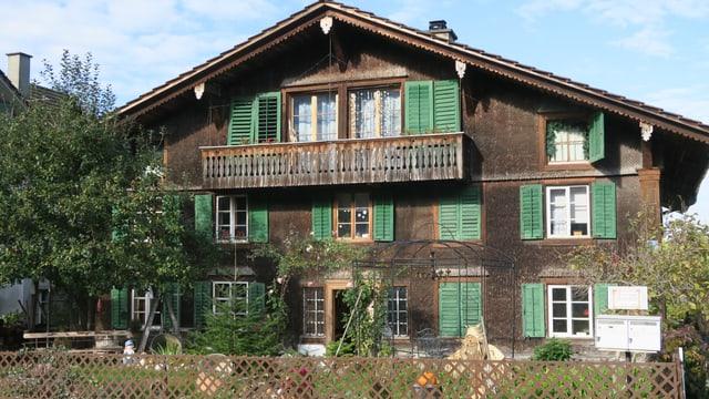 Altes Holzhaus aus dem 17. Jahrhundert mit grünen Fensterläden.