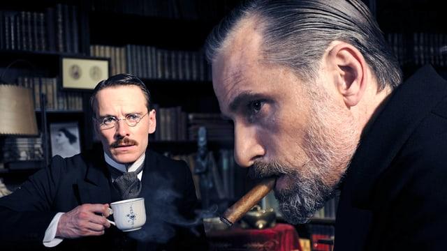Zwei elegant bekleidete Herren sitzen in einem Büro. Der eine hält eine Tasse in der Hand und der andere raucht eine Zigarre.