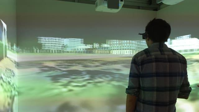 Mann steht in einem Raum. An den Wänden ist eine virtuelle Stadt projeziert. Er trägt eine 3D-Brille.