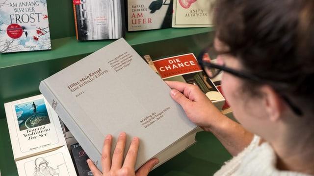 Eine Leserin schaut auf die Titelseite eines Buches