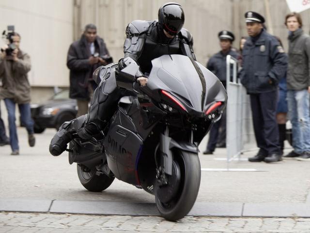 Robocop sitzt in Rüstung auf einem Motorrad.