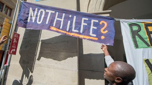 """Ein violettes Plakat hängt an einer Mauer. Auf dem Banner steht: """"Nothilfe""""?"""