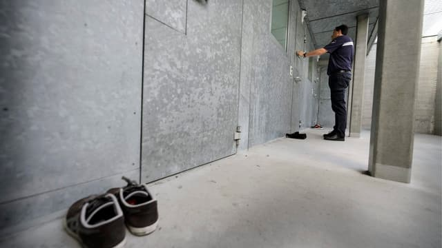 Ein Wärter schliesst eine Gefängnistüre.