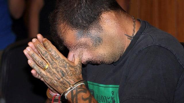 Der Bankräuber in Handschellen bei seiner Verhaftung 2013 in Thailand.