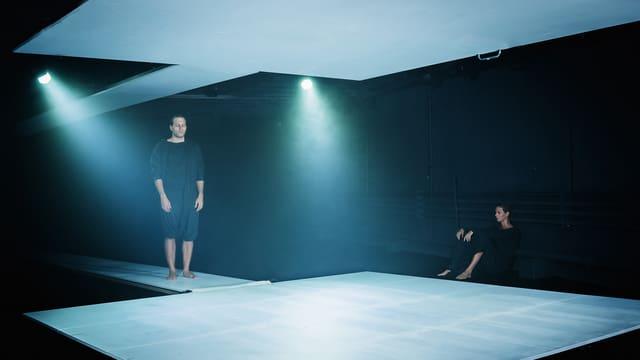 Ein Mann und eine Frau. Er steht auf einer weissen Bühne - sie sitzt daneben. Zwei Scheinwerferspot beleuchten die Szene.