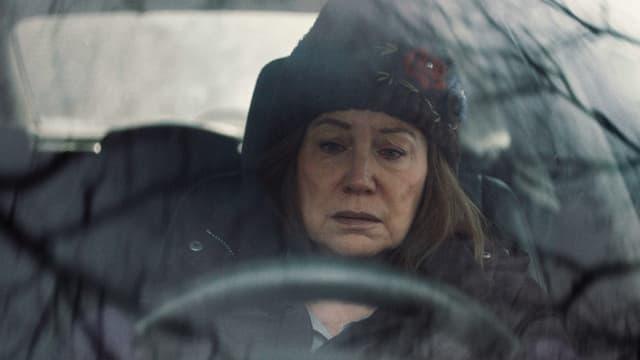 Eine Frau mit traurigem Gesicht sitzt in Winterkleidung im Auto.
