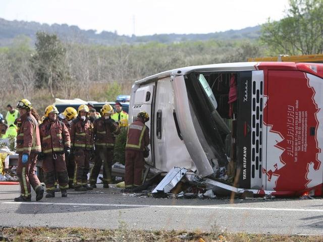 Umgekippter und demolierter Bus, Rettungskräfte daneben.