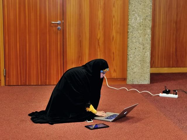 Eine iranische Fernsehjournalistin kniet an der Atomkonferenz in Genf von vergangenem November am Boden, vor ihr der Laptop, das Tablet und das Smartphone. Sie wartet auf ihren Einsatz in den Medien im Iran.