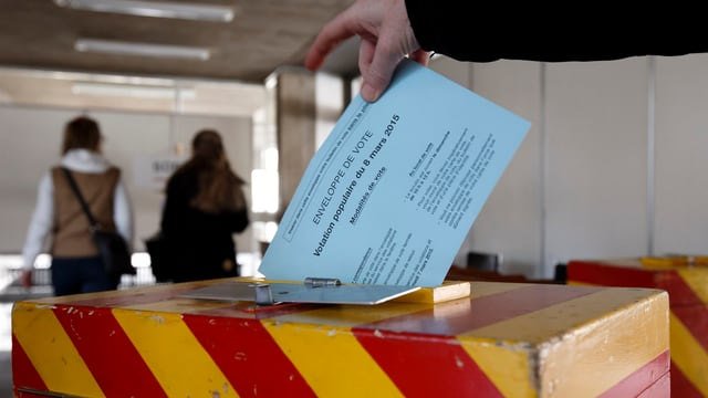 Cedel da votaziun vegn mess en in'urna da votar
