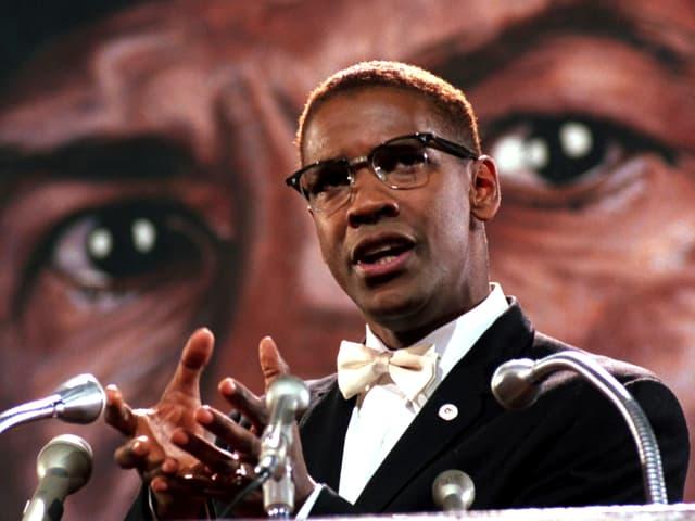 Washington im Anzug mit Fliege an einem Rednerpult mit vier Mikrofonen. Im Hintergrund ein grosses Augenpaar.