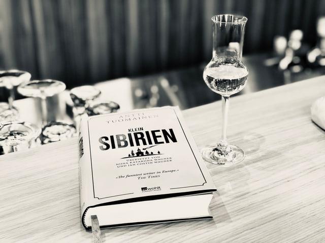 «Klein-Sibirien» von Antti Tuomainen liegt auf einem Tresen. Daneben steht ein Glas mit Schnaps.
