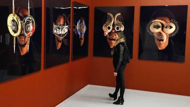 Ein Raum mit roten Wänden: Darauf Gesichter mit technisch anmutenden Masken.