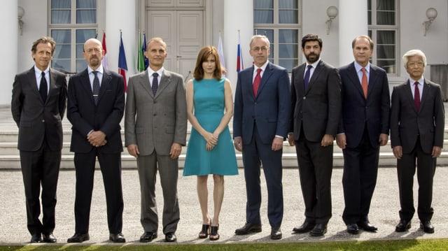 Acht Personen stehen nebeneinander und posieren für ein Foto.