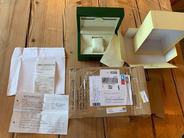 Leere Boxen und Schachteln, ein Zertifikat für eine Rolex-Uhr