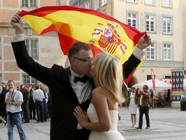 Ein Brautpaar küsst sich, im Hintergrund die spanische Flagge.