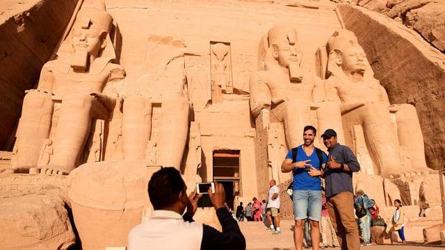 Touristen fotographieren sich vor dem Eingang zum Tempel