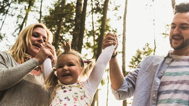Das Bild zeigt Vater und Mutter mit ihrer Tochter beim Spielen.