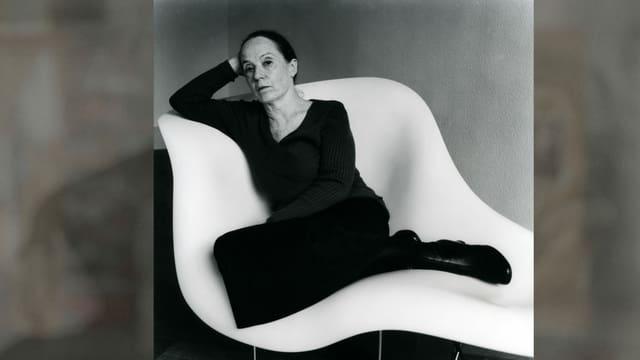 Frau sitzt auf einem weissen Stuhl
