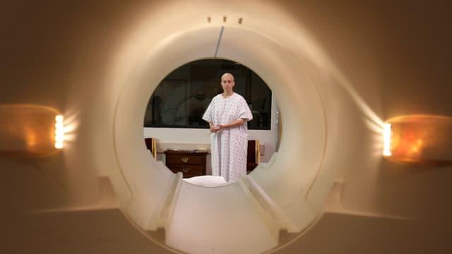 Eine Frau mit rasiertem Kopf schaut auf die Liege eines MRI-Scanners.