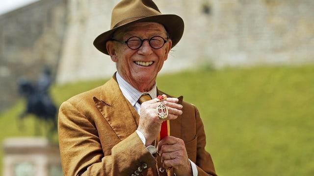Schauspieler John Hurt präsentiert die erhaltene Ritterauszeichnung mit einem Lächeln auf dem Gesicht.