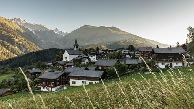 Ein Dorf im Morgenlicht, dahinter verschneite Berge.