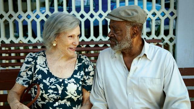 Das ältere Paar sitzt auf einer Bank und lacht zusammen.