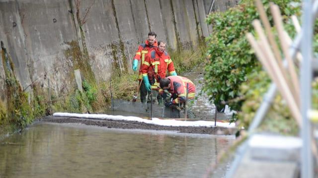 Rettungskräfte errichten Ölsperren am Eibach in Tecknau.