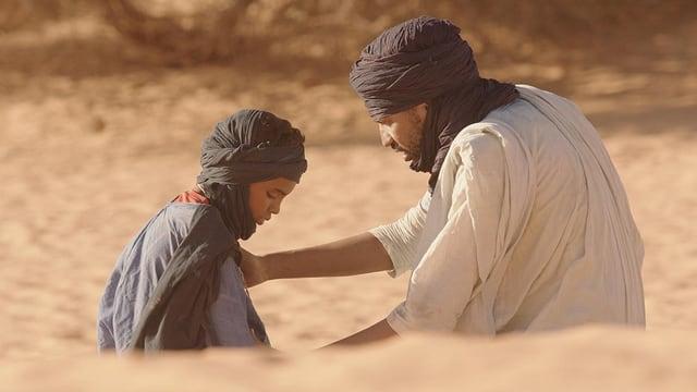 Ein Mann und ein Junge mit Turbanen sitzen in einer Wüste am Boden.