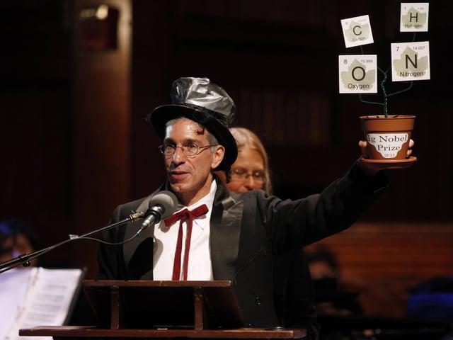 Mann mit Zylinder hebt Blumentopf zur Eröffnung der lg-Nobelpreisverleihung in die Höhe.
