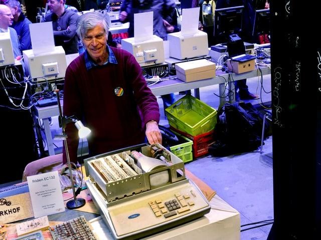 Mann präsentiert einen alten Computer.