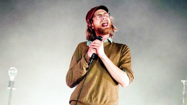 Ein junger Mann mit langen Haaren, Briller und Mütze hält ein Mikrofon in der Hand und singt inbrünstig mit geschlossenen Augen.