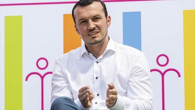 Ein Mann mit Mikrofon sitzt vor einer farbigen Plakatwand.