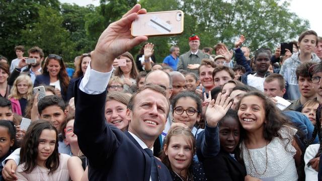 Macron macht ein Selfie mit jugendlichen Fans.