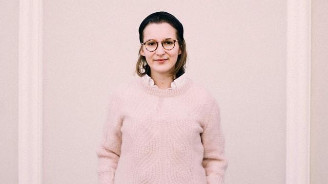 Frau mit Brille steht vor einer Wand.