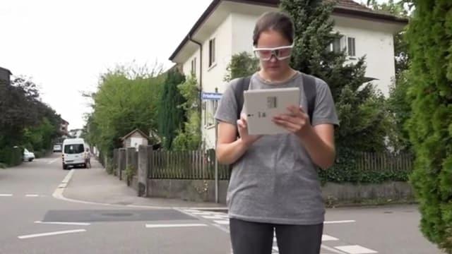 Eine Frau mit einem Tablet auf der Strasse.