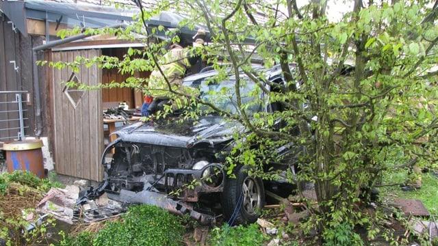 Ein stark beschädigtes Fahrzeug mitten in einem Garten.