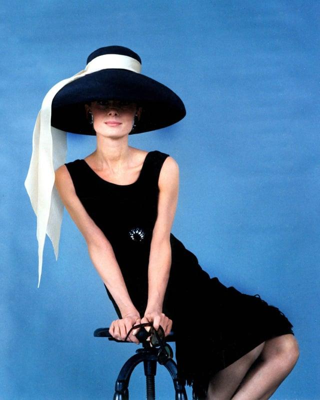 Audrey Hepburn mit kurzem schwarzen Kleid und Hut.